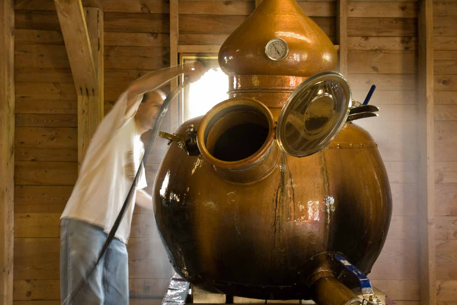 Keith Bodine, of Sweetgrass Winery and Distillery, cleaning his pot still.