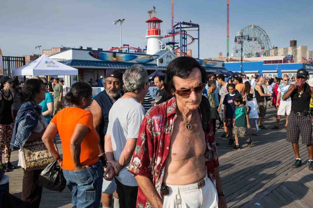 A a man in the crowd on the Coney Island boardwalk.