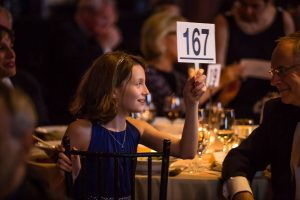 A girl bids for her family at the New York Pops gala