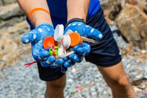 A handful of plastic trash washed up on a shore, during a shoreline cleanup in conjunction with Riverkeepers. Photographed for Morgan Stanley.