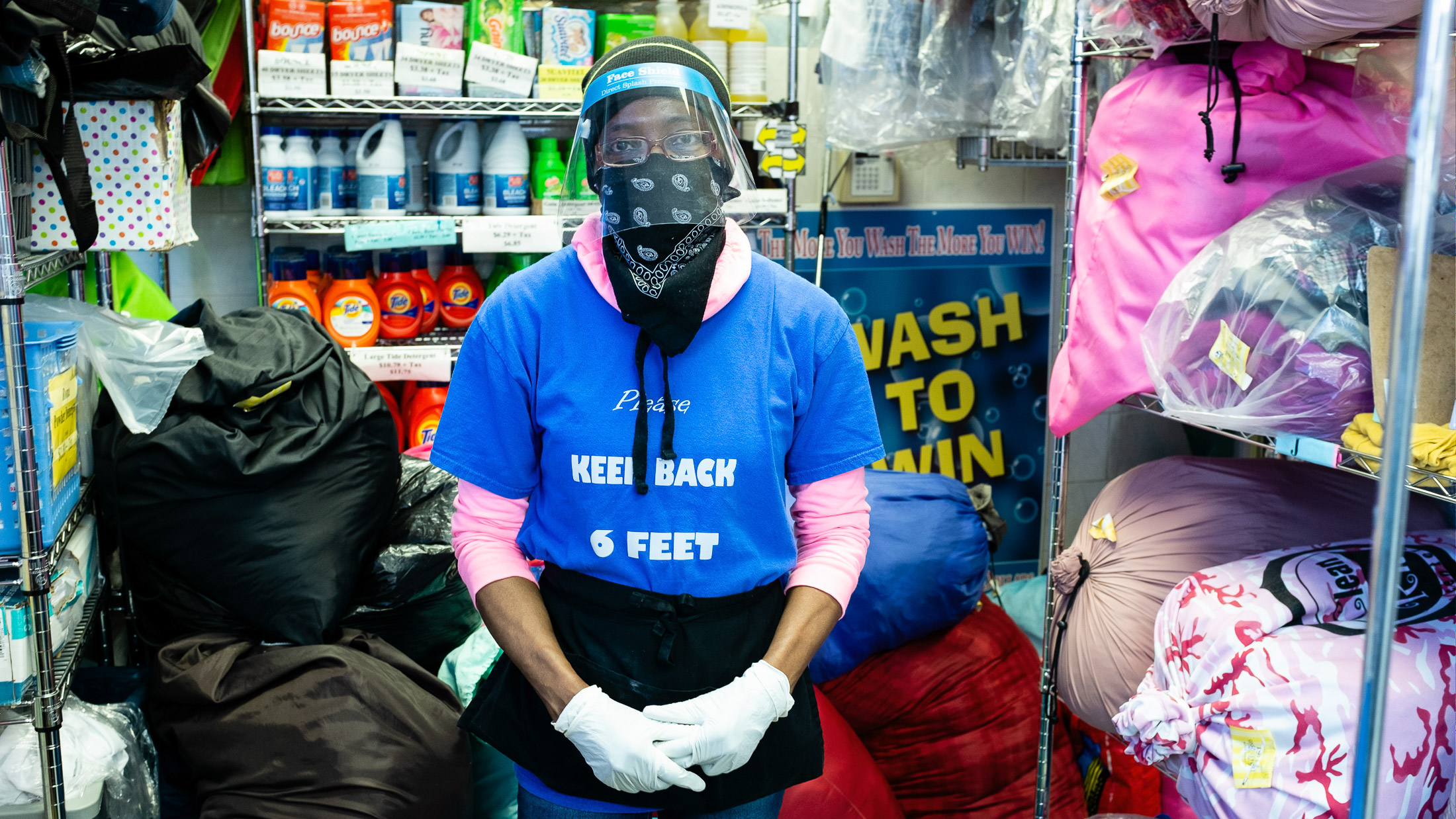 Laundromat attendant with face shield and T-shirt